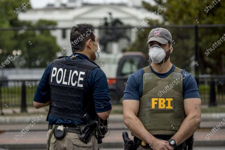 The White House is visible behind a large security fence as uniformed Secret Service and FBI agents stand on the street in front of Lafayette Park in the morning hours in Washington, as protests continue over the death of George Floyd. Floyd died after being restrained by Minneapolis police officers