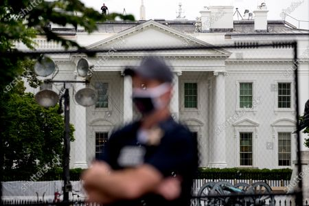 The White House is visible behind a large security fence as a uniformed Secret Service agent stands on the street in front of Lafayette Park in the morning hours in Washington, as protests continue over the death of George Floyd. Floyd died after being restrained by Minneapolis police officers