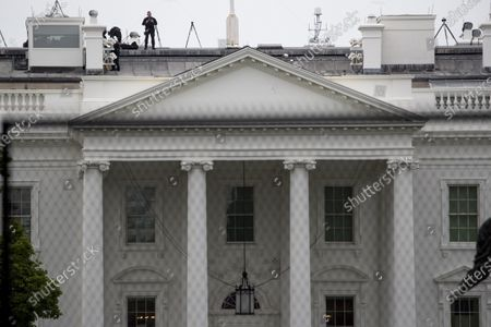 Uniformed Secret Service agent stands on the roof of the White House in the morning hours in Washington, as protests continue over the death of George Floyd. Floyd died after being restrained by Minneapolis police officers