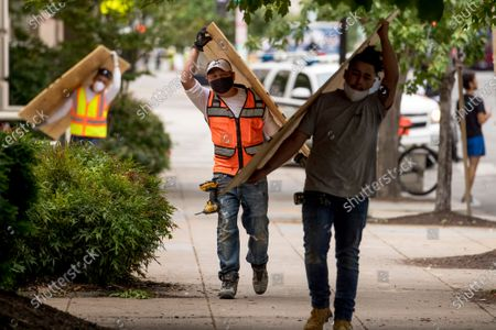Workers carry large wood boards past the historical St. John's Episcopal Church across Lafayette Park from the White House in the morning hours in Washington, as protests continue over the death of George Floyd. Floyd died after being restrained by Minneapolis police officers