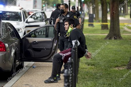 Lewis Sanchez, center, sits after being handcuffed by Secret Service agents along Constitution Avenue near the White House in the morning as protests continue over the death of George Floyd in Washington, . Floyd died after being restrained by Minneapolis police officers. Sanchez and three other friends were stopped as they returned to their car after spending the night at a strangers home because of a District of Columbia city wide curfew. Agents later released Sanchez