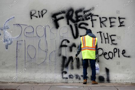 Worker removes graffiti from a building, in Washington, following protests over the death of George Floyd, who died after being restrained by Minneapolis police officers