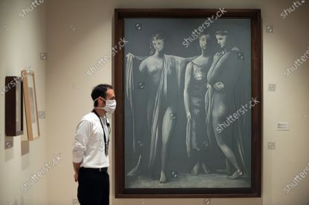 """A man wearing a facemask stands next to a painting during the exhibition """"Dialogues with Picasso: collection 2020-2023"""" at Picasso Museum.  The new permanent collection arrives at the museum with 120 works organised by Almine Foundation, Bernard Ruiz-Picasso for the Art (FABA) and supported by the artistic team of the Picasso Museum. This exhibition has artworks as important as a tapestry based on the original paintings of 'The ladies of Avignon', the cubist sculpture 'Glass of absinthe' or the painting 'Susanna and the elders'."""