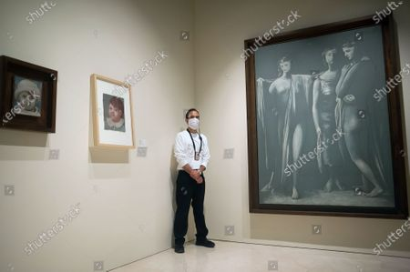 """An employee wearing a face mask is stands in a corner in between a display of paintings during the exhibition """"Dialogues with Picasso: collection 2020-2023"""" at Picasso Museum.  The new permanent collection arrives at the museum with 120 works organised by Almine Foundation, Bernard Ruiz-Picasso for the Art (FABA) and supported by the artistic team of the Picasso Museum. This exhibition has artworks as important as a tapestry based on the original paintings of 'The ladies of Avignon', the cubist sculpture 'Glass of absinthe' or the painting 'Susanna and the elders'."""