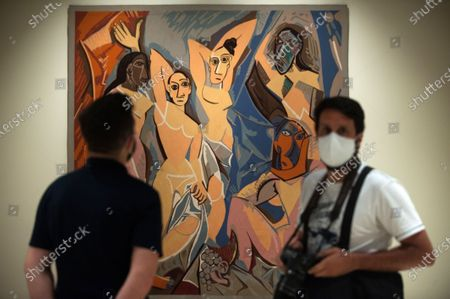 """A photographer wearing a face mask stand infront of the painting of 'The ladies of Avignon' displayed during the exhibition """"Dialogues with Picasso: collection 2020-2023"""" at Picasso Museum.  The new permanent collection arrives at the museum with 120 works organised by Almine Foundation, Bernard Ruiz-Picasso for the Art (FABA) and supported by the artistic team of the Picasso Museum. This exhibition has artworks as important as a tapestry based on the original painting of 'The ladies of Avignon', the cubist sculpture 'Glass of absinthe' or the painting 'Susanna and the elders'."""
