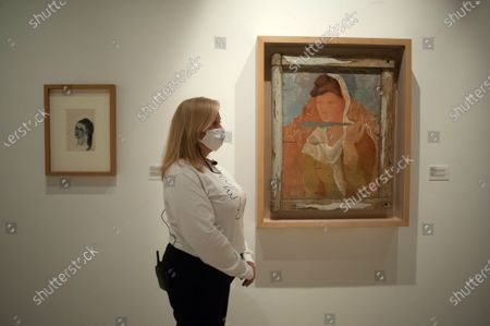 """Stock Photo of A woman, wearing a face mask stands next to a painting displayed during the exhibition """"Dialogues with Picasso: collection 2020-2023"""" at Picasso Museum. The new permanent collection arrives at the museum with 120 works organised by Almine Foundation, Bernard Ruiz-Picasso for the Art (FABA) and supported by the artistic team of the Picasso Museum. This exhibition has artworks as important as a tapestry based on the original paintings of 'The ladies of Avignon', the cubist sculpture 'Glass of absinthe' or the painting 'Susanna and the elders'."""