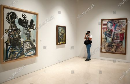 """A photographer is seen taking pictures as he stands between paintings displayed during the exhibition """"Dialogues with Picasso: collection 2020-2023"""" at Picasso Museum.  The new permanent collection arrives at the museum with 120 works organised by Almine Foundation, Bernard Ruiz-Picasso for the Art (FABA) and supported by the artistic team of the Picasso Museum. This exhibition has artworks as important as a tapestry based on the original paintings of 'The ladies of Avignon', the cubist sculpture 'Glass of absinthe' or the painting 'Susanna and the elders'."""