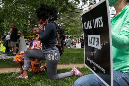 """Ericka Ward-Audena, of Washington, touches her daughter's chin, covered in a coronavirus precaution face mask, as she and Elle Ward-Audena, 7, take a knee in front of a police line during a protest of President Donald Trump's visit to the Saint John Paul II National Shrine, in Washington. """"I wanted my daughter to see the protests, it's really important. I've gotten a million questions from her because of it,"""" says Ward-Audena, """"I think the most egregious statement was 'when they start looting, we start shooting.' That crossed a line for me."""" Protests continue over the death of George Floyd, who died after being restrained by Minneapolis police officers"""