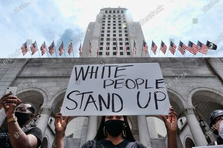 Protester holds a sign during a Black Lives Matter protest over the death of George Floyd outside of Los Angeles City Hall . Floyd, a black man died after being restrained by Minneapolis police officers on May 25