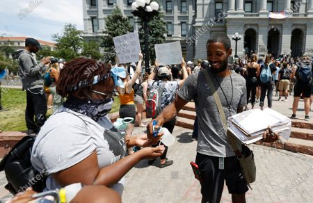 Devin Frank, right, dispenses hand sanitizer after collecting a signature for a statewide ballot from a demonstrator, during a protest outside the State Capitol in Denver over the death of George Floyd, a handcuffed black man in police custody in Minneapolis