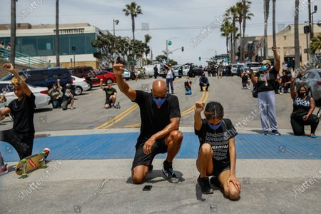 Boris Kodjoe, center and his daughter Sophie,15, take a knee and raise a fist, after a rally and march by hundreds of people, in protest of the death of George Floyd and in support of Black Lives Matter, near the Manhattan Beach Pier