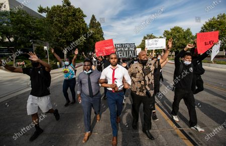 MORENO VALLEY, CA - JUNE 2, 2020: Kevin Carrington, left, Pastor Michael Kelly, middle, of Mt Rubidoux Church and Marquis Johns, right, lock arms to lead demonstrators on a march to the police station to protest the death of George Floyd's during the coronavirus pandemic on June 2, 2020 in Moreno Valley, California. (Gina Ferazzi / Los Angeles Times)