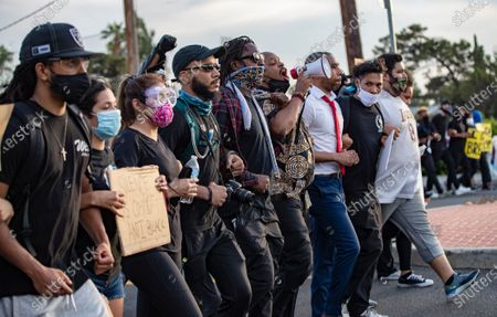 Marquis Johns with the bullhorn locks arms with Pastor Michael Kelly, right, leading hundred of demonstrators on a march to protest the death of George Floyd's during the coronavirus pandemic on June 2, 2020 in Moreno Valley, California. (Gina Ferazzi / Los Angeles Times)