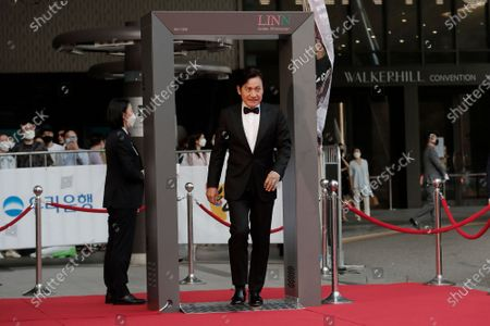 South Korean actor Ahn Sung-ki walks through a thermal camera system to check the body temperature as he arrives on the red carpet at the 56th Daejong Film Awards ceremony in Seoul, South Korea