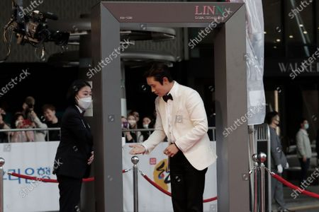 South Korean actor Lee Byung-hun receives hand sanitizer before passing through a thermal camera system to check the body temperature as he arrives on the red carpet at the 56th Daejong Film Awards ceremony in Seoul, South Korea