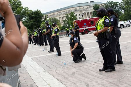 A Capitol Police Officer kneels before protestors who gathered at the United States Capitol in Washington D.C., U.S., after George Floyd died in police custody in Minnesota.