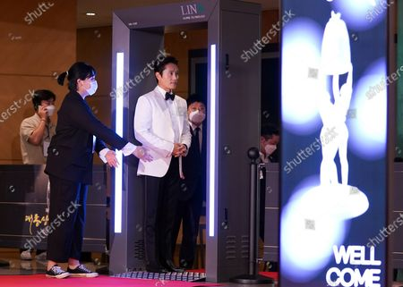 Lee Byung-hun checks the temperature after the photo call for the 2020 Daejong Film Award