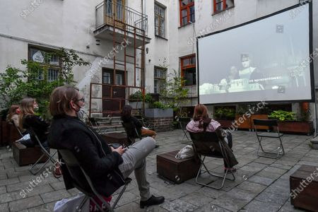Stock Photo of People watch black comedy movie directed by Yorgos Lanthimos 'The Favourite' in an outdoor cinema at a patio, amid the ongoing coronavirus COVID-19 pandemic in Lublin, eastern Poland, 03 June 2020.