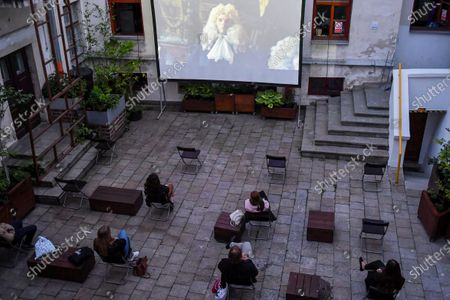 People watch black comedy movie directed by Yorgos Lanthimos 'The Favourite' in an outdoor cinema at a patio, amid the ongoing coronavirus COVID-19 pandemic in Lublin, eastern Poland, 03 June 2020.
