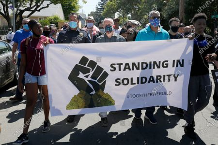 Sacramento Police Chief Daniel Hahn, behind banner, left, Mayor Darrell Steinberg, center, and Pastor Anthony Sadler, right, march shoulder to shoulder, to the Shiloh Baptist Church in honor of George Floyd, in Sacramento, Calif. Floyd, a black man, died after being restrained by Minneapolis police officers on Memorial Day, May 25, 2020