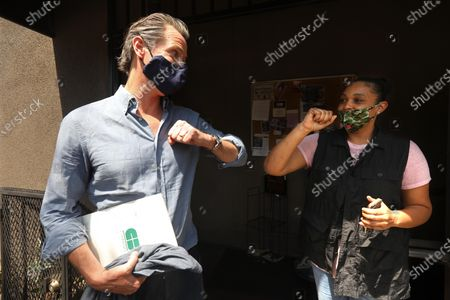 Stock Picture of California Governor Gavin Newsom prepares to connect elbows with Candace O'Connor, owner of Brimberry Barber and Beauty Salon, after she shared her thoughts on running a business in the time of COVID-19 and the recent protests in Los Angeles, California, USA, on 03 June 2020.