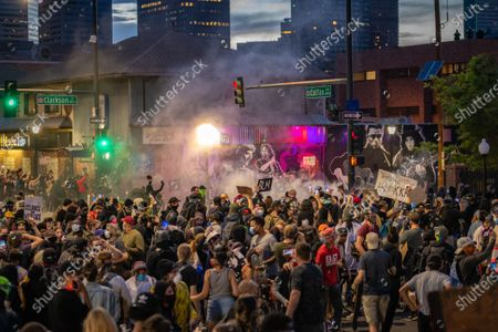 Large group of Protesters in street being tear gassed, large cloud, with city skyline at dusk in background