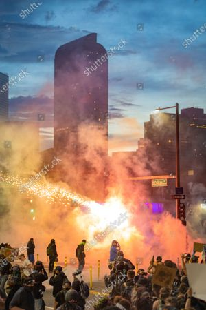 Large group of protesters with tear gas cloud of smoke and firework exploding and Denver city skyscrapers in background at dusk