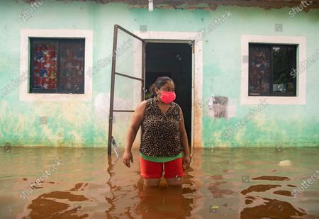 Stock Image of A woman navigates a flooded street near her home in Tecoch, Yucatan, Mexico, 03 June 2020. According to reports, Tropical Storm Cristobal will remain in in the Gulf of Mexico for a couple of days, causing torrential rains in some coastal areas.