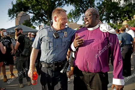 Kansas City police Chief Rick Smith walks away from a crowd of protesters to talk with organizer Bishop Tony Caldwell, in Kansas City, Mo., during a unity march to protest against police brutality following the death of George Floyd, who died after being restrained by Minneapolis police officers on May 25