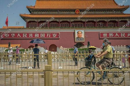 A man wearing a protective face mask rides a bicycle past tourists and policemen in front of the Chairman Mao portrait on the south gate of the Forbidden City, near the Tiananmen Square, in Beijing, China, 04 June 2020. 04 June 2020 marks the 31st anniversary of the 1989 Tiananmen Square protests. Between 15 April and 04 June 1989, students, intellectuals, and activists engaged in a series of demonstrations against the Chinese Communist Party where the subsequent crackdown by authorities caused many civilians' deaths and injuries. Since then, no official death toll has been released by Chinese officials. However, rights groups estimate hundreds if not thousands were killed while many people were jailed in a subsequent purge. The Tiananmen Square protest remains one of the most widely censored topics in China.