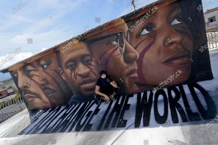 Italian street artist Jorit Agoch poses in front of his latest work, a huge mural in memory of George Floyd, in Naples, southern Italy, 04 June 2020. The 46-year-old Floyd died in police custody in Minneapolis, Minnesota, USA on 25 May 2020, after police officer Derek Chauvin pressed a knee on the neck of the handcuffed African-American man lying on the ground for almost nine minutes, reports state. Faces of Lenin, Martin Luther King, Malcom X and Angela Davis are also painted on the mural.