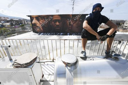 Italian street artist Jorit Agoch poses next to his latest work, a huge mural in memory of George Floyd, in Naples, southern Italy, 04 June 2020. The 46-year-old Floyd died in police custody in Minneapolis, Minnesota, USA on 25 May 2020, after police officer Derek Chauvin pressed a knee on the neck of the handcuffed African-American man lying on the ground for almost nine minutes, reports state. Faces of Lenin, Martin Luther King, Malcom X and Angela Davis are also painted on the mural.