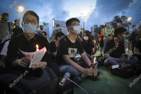 Hong Kong democracy activist Joshua Wong, center, holds a candle as he joins others for a vigil for the victims of the 1989 Tiananmen Square Massacre at the Victoria Park in Causeway Bay, Hong Kong, Thursday, despite permission for it being officially denied. China is tightening controls over dissidents while pro-democracy activists in Hong Kong and elsewhere try to mark the 31st anniversary of the crushing of the pro-democracy movement in Beijing's Tiananmen Square