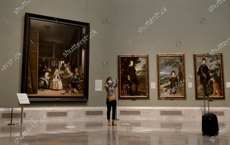 A woman wearing a face mask takes a selfie in front of the painting 'Las Meninas' (L) by Spanish artist Diego Velazquez, during the presentation of the exhibition 'Reunion' at the Prado Museum in Madrid, Spain, 04 June 2020. The Prado Museum will reopen to the public on 06 June with 'Reunion,' an exhibition that features its permanent collection's most emblematic artworks and will until 13 September 2020.