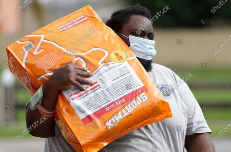 Miami-Dade County Animal Services Department employee Antonio Smith prepares to load a bag of dog food into a car at a Drive-Thru Pet Food Bank at Lake Stevens Park, in Miami Gardens, Fla. About 40,000 lbs of dog and cat food donated by the American Society for the Prevention of Cruelty to Animals as part of their national ASPCA COVID-19 Relief & Recovery Initiative were distributed Thursday