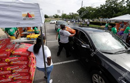 Employees and volunteers at a Miami-Dade County Animal Services Department Drive-Thru Pet Food Bank load pet food into cars at Lake Stevens Park, in Miami Gardens, Fla. About 40,000 lbs of dog and cat food donated by the American Society for the Prevention of Cruelty to Animals as part of their national ASPCA COVID-19 Relief & Recovery Initiative were distributed Thursday