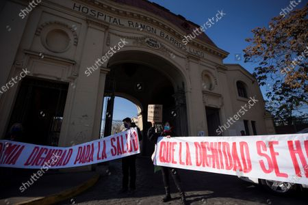 Stock Image of Activists hold up banners during a healthcare professionals' and consumers' groups protest against the management of the ongoing pandemic of the COVID-19 disease caused by the SARS-CoV-2 coronavirus by the government of President Sebastian Pinera and Health Minister Jaime Manalich held in front of the Barros Luco Trudeau Hospital in the commune of San Miguel in Santiago de Chile, Chile, 04 June 2020.