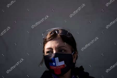 Stock Photo of A woman wears a face mask emblazoned with a Chilean flag in the shape of a medical cross symbol during a healthcare professionals' and consumers' groups protest against the management of the ongoing pandemic of the COVID-19 disease caused by the SARS-CoV-2 coronavirus by the government of President Sebastian Pinera and Health Minister Jaime Manalich held in front of the Barros Luco Trudeau Hospital in the commune of San Miguel in Santiago de Chile, Chile, 04 June 2020.