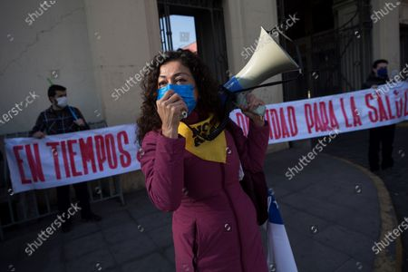 A woman wears a face mask and speaks through a megaphone during a healthcare professionals' and consumers' groups protest against the management of the ongoing pandemic of the COVID-19 disease caused by the SARS-CoV-2 coronavirus by the government of President Sebastian Pinera and Health Minister Jaime Manalich held in front of the Barros Luco Trudeau Hospital in the commune of San Miguel in Santiago de Chile, Chile, 04 June 2020.