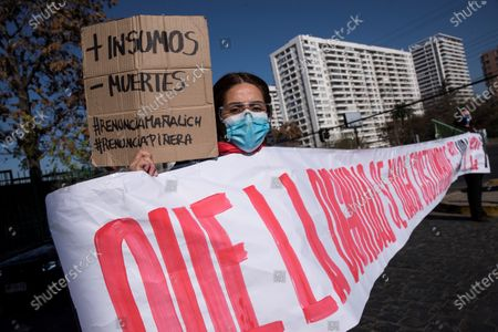A woman wears a face mask and holds up a placard reading in Spanish: 'More Resources, Fewer Deaths #ManalichResign #PineraResign' during a healthcare professionals' and consumers' groups protest against the management of the ongoing pandemic of the COVID-19 disease caused by the SARS-CoV-2 coronavirus by the government of President Sebastian Pinera and Health Minister Jaime Manalich held in front of the Barros Luco Trudeau Hospital in the commune of San Miguel in Santiago de Chile, Chile, 04 June 2020.