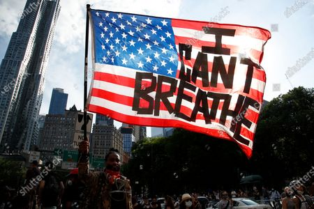 A protester holds an American Flag with the words 'I Can't Breathe' as he walks in Manhattan after a George Floyd Memorial demonstration in Cadman Plaza in Brooklyn, New York, USA, 04 June 2020. A bystander's video posted online on 25 May, appeared to show George Floyd, 46, pleading with arresting Minneapolis Police officers that he couldn't breathe as an officer knelt on his neck. The unarmed Black man later died in police custody. According to news reports on 29 May, Derek Chauvin, the police officer in the center of the incident has been taken into custody and charged with murder in the George Floyd killing. On 03 June three other officers on scene were charged with aiding and abetting murder of second degree.