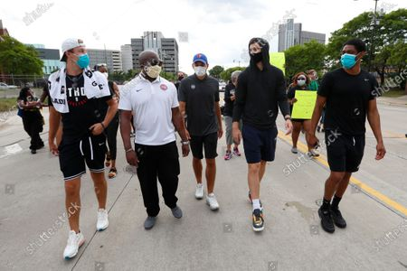Detroit Pistons guard Luke Kennard, from left, Cletus Lewis Jr., Senior Director of Public Relations; Jordan Brink, Player Development Coach and Head Video Coordinator; guard Sviatoslav Mykhailiuk and guard Brandon Knight walk with protesters in Detroit, over the death of George Floyd, a black man who was in police custody in Minneapolis. Floyd died after being restrained by Minneapolis police officers on Memorial Day