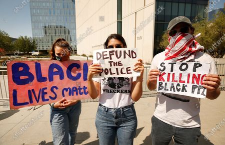Stock Photo of Laurel Sager, Giulia Alexander and Michael Parks Randa, left to right, hold signs of protest in front of LAPD Headquarters Thursday morning hoping to join a larger protest scheduled for later in the day near LA City Hall. National Guardsmen remain on patrol surrounding the police headquarters with only a few protestors in sight.