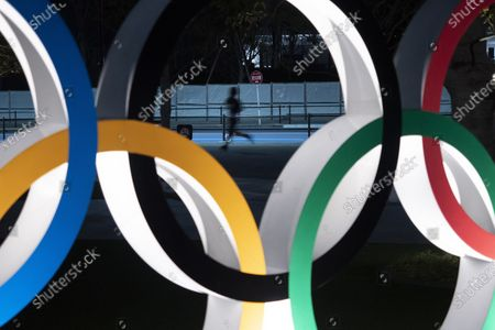A man jogs past the Olympic rings in Tokyo. Former Olympic minister Toshiaki Endo said at a meeting of the ruling Liberal Democratic Party, that a decision of whether to hold the Games should be made around March, which is a crucial time to finalize participating athletes, NHK said