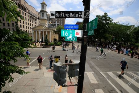 """With St. John's Church in the background, people walk under a new street sign, in Washington. """"The section of 16th street in front of the White House is now officially 'Black Lives Matter Plaza,'"""" District of Columbia Mayor Muriel Bowser tweeted. The black and white sign was put up to mark the change"""