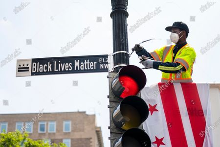A city worker changes the name of a section of 16th Street to 'Black Lives Matter Plaza' in Washington, DC, USA, 05 June 2020.  The street is across from the White House and is the location of seven days of protests in DC over the death of George Floyd. Earlier in the day, with permission from the city, volunteers painted the words 'Black Lives Matter' in giant letters on the street. DC Mayor Muriel Bowser renamed that section of 16th Street Black Lives Matter Plaza.
