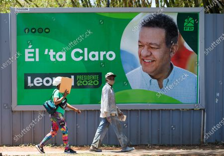 People pass an election campaign poster of presidential candidate Leonel Fernandez in Santo Domingo, Dominican Republic, 05 June 2020. The country is already immersed in the electoral campaign for the presidential and legislative elections on 05 July, while looking askance at the behavior of the pandemic, which has already forced to postpone this appointment with the ballot boxes once.