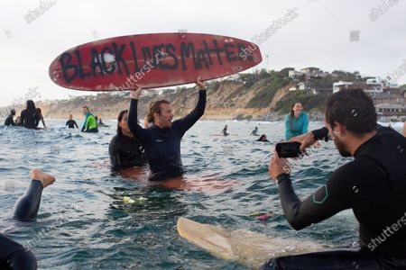 Protesters chant Black Lives Matter during a paddle out in solidarity with other national demonstrations showing outrage over the death of George Floyd in Moonlight State Beach. In surfing culture, paddle outs are held as a way to memorialize those who have lost their lives, or momentarily reflect on a time or issue.