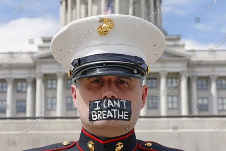 Retired Marine Todd Winn protests in front of the Utah State Capitol, in Salt Lake City