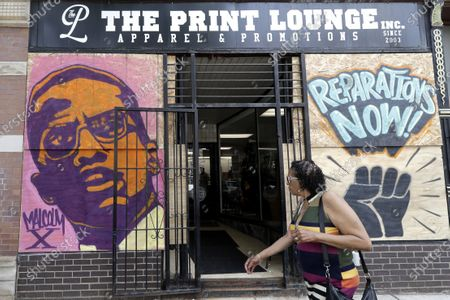 Woman walks past a painting of Malcolm X at a retail store in the Pilsen neighborhood, in Chicago. Chicago artists use boarded-up storefronts